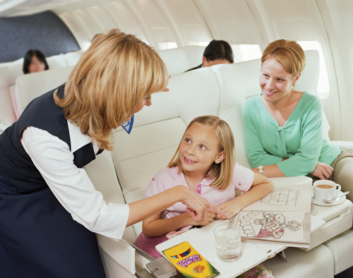 Mother and Daughter on Long Flight. Stewardess plays with child.