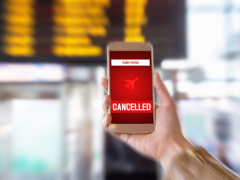 Hand holding mobile phone with cancelled flight on screen