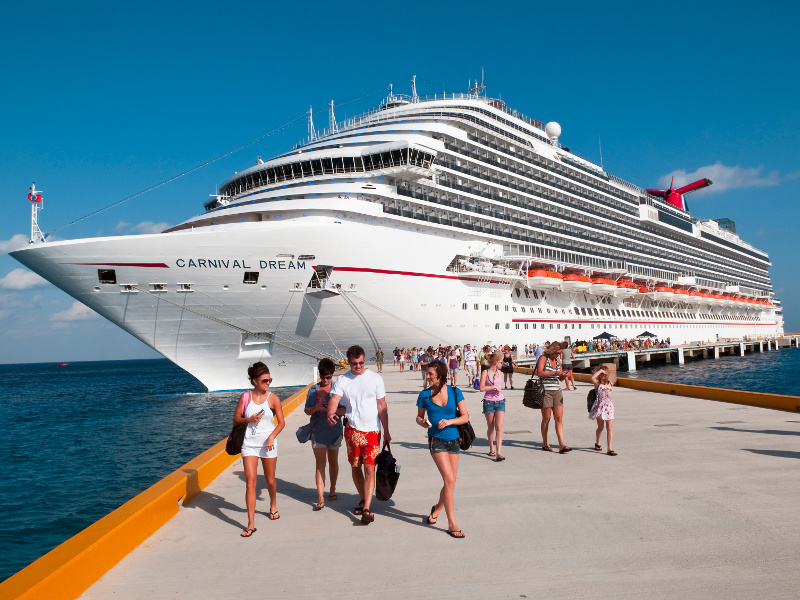 Passengers disembark from their cruise ship and prepare to explore the port.