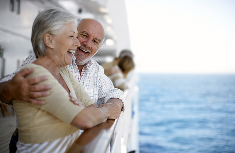 A senior couple takes in the view from a cruise ship.