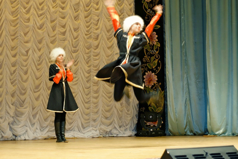 Traditional Russian dancer jumps in the air with arms outstretched while the other claps at a show for travellers.