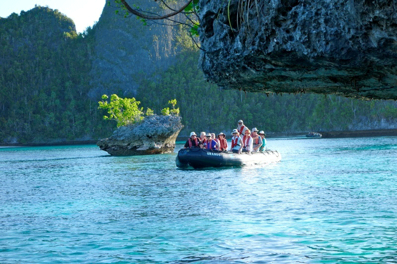 People on a boat in the Karst Spice Islands near eroding rocks.