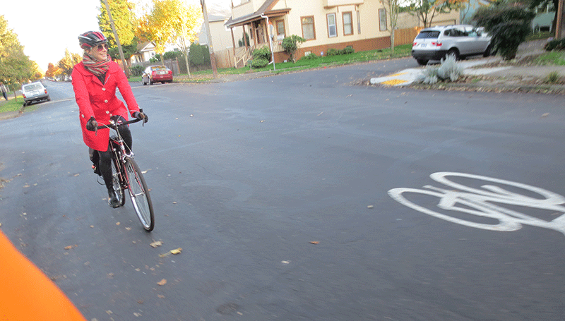 The author riding her bicycle along a dedicated bike path in Portland, Oregon.