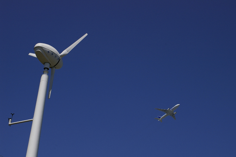Windmill with airplane flying directly above.