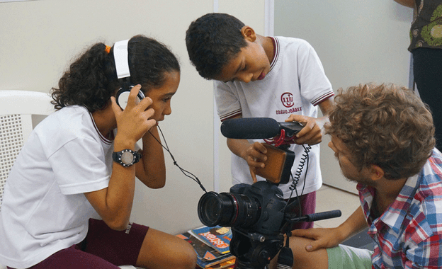 Children learning to use camera equipment