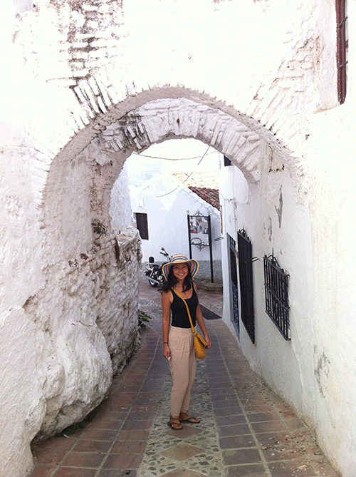 Photo of a lady standing in an archway wearing sandals and a hat in Comares Andalucia