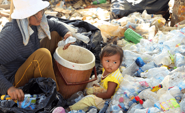 Impoverished families sorting through landfill garbage
