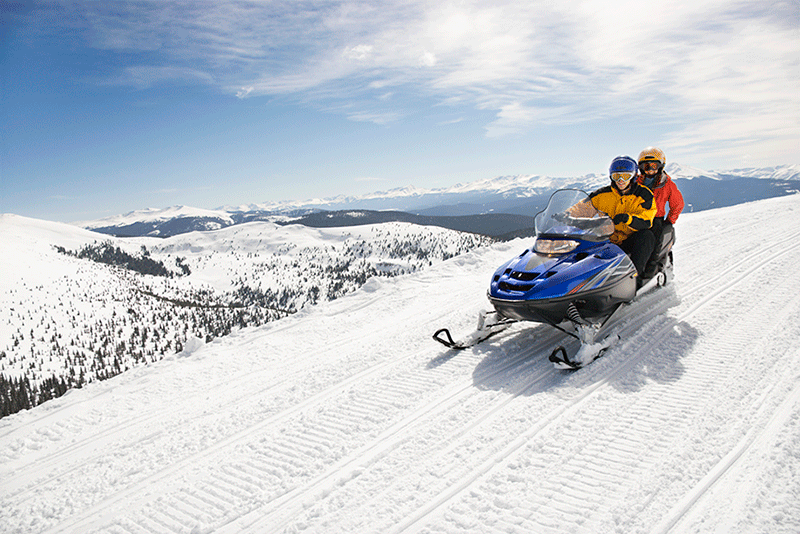 Couple sitting together on a snowmobile, riding through a scenic mountain pass.