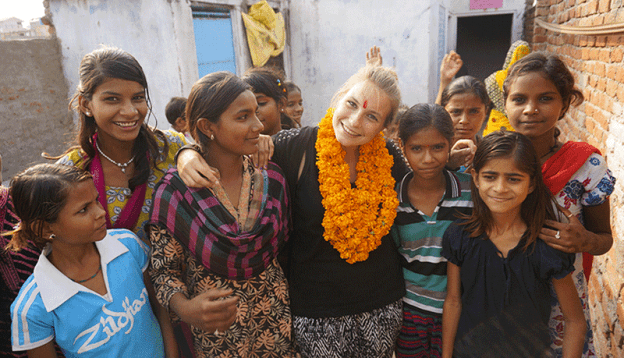 Young volunteer traveller surrounded by girls in India.