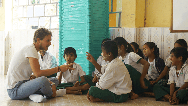 Young volunteer traveller plays with Burmese school children