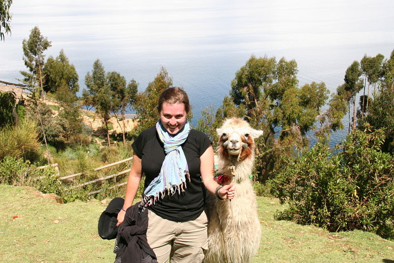 Girl Smiling beside Llama at Lake Titicaca Bolivia
