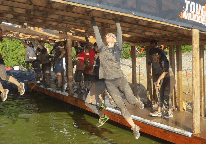 Our Executive Director, Kathy Starko, battling the Funky Monkey at Tough Mudder 2014. She made it across!