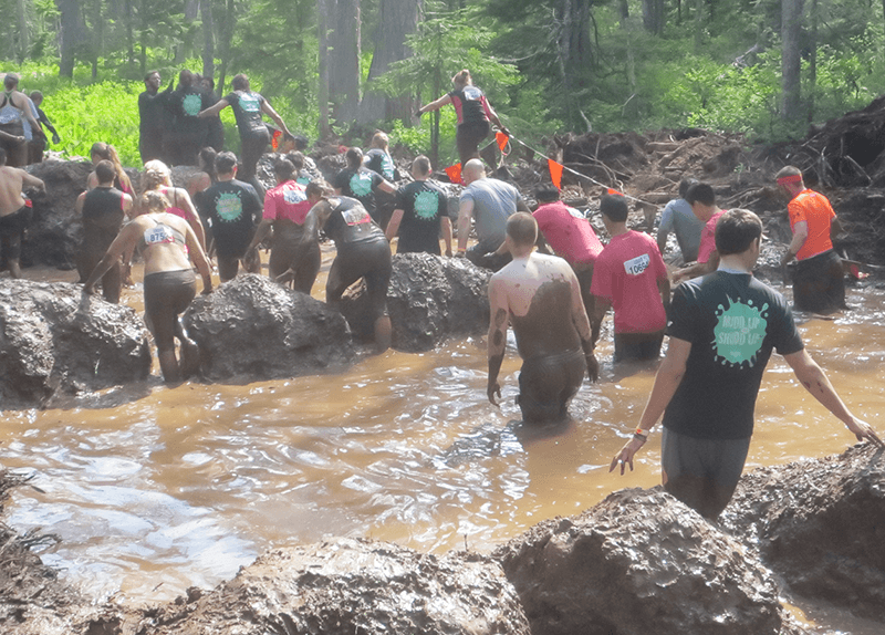 People slipping and sliding through the Mud Mile Obstacle 2014