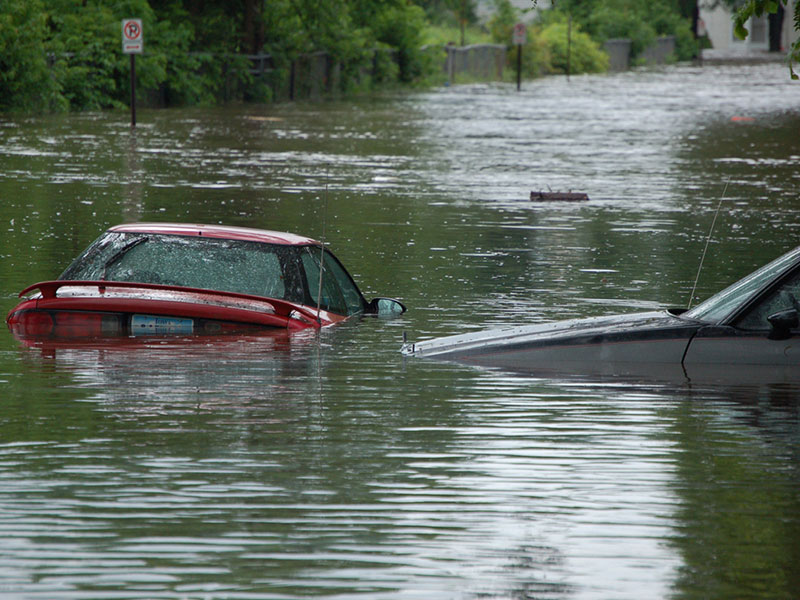 Photo of cars trying to drive on a flooded road on a trip