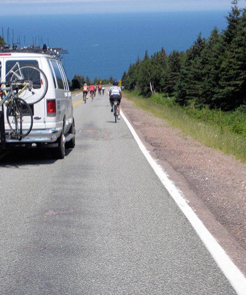 Cyclists riding down a steep hill on Cabot Trail toward the ocean followed by a silver SUV.