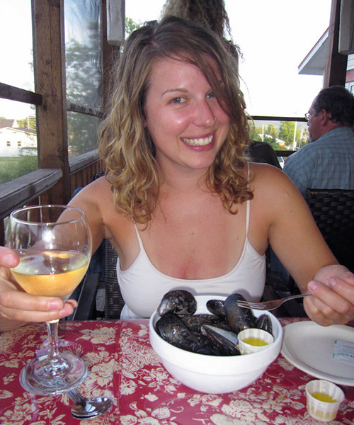 Customer enjoying white wine and mussels at Baddeck Lobster Suppers restaurant.