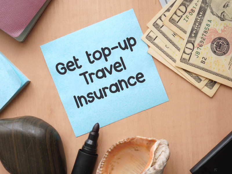 "Sticky note with ""get top-up travel insurance"" written on it."
