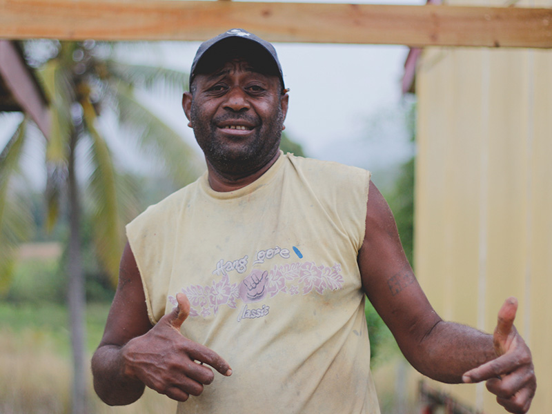 Fijian man wearing a baseball cap and t-shirt posing for a photo with thumbs up.