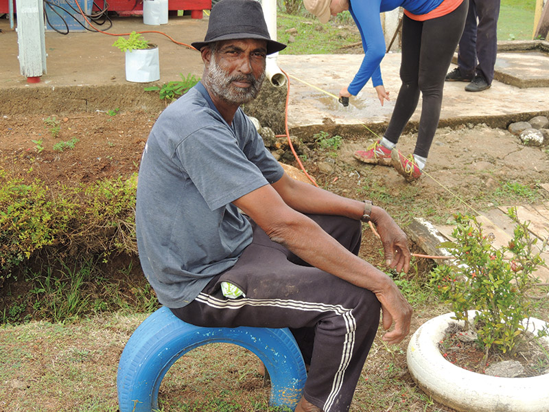 Photo of a Fijian man sitting on a tire, taken as part of a volunteer program there.