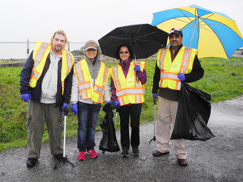 TuGo employees volunteering at rainy Garry Point Park