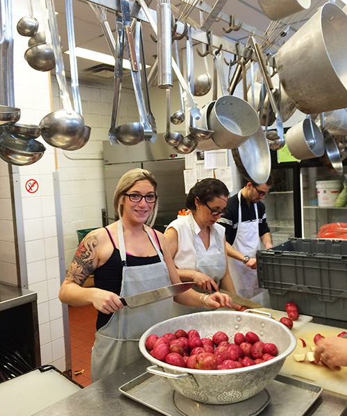 TuGo employee volunteers cutting potatoes at Old Brewery Mission Montreal.