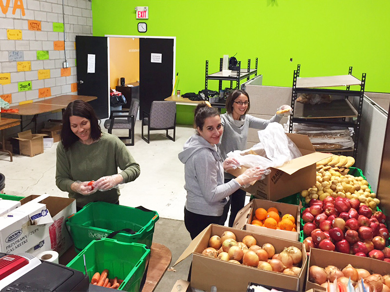 Mississauga volunteers organizing various fruits and vegetables into different containers.