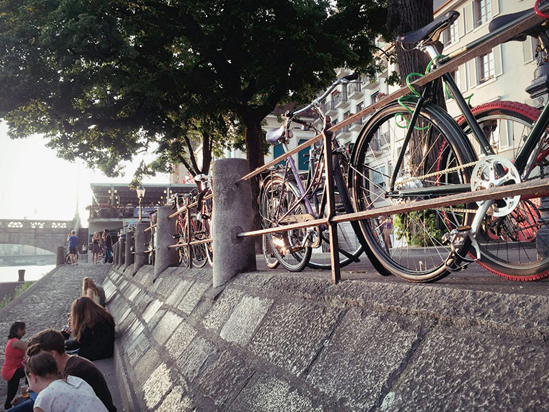 Cyclists relax along the rhine in basel switzerland
