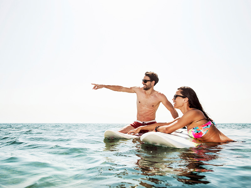 active couples try surfing honeymoon vacation covered by travel insurance