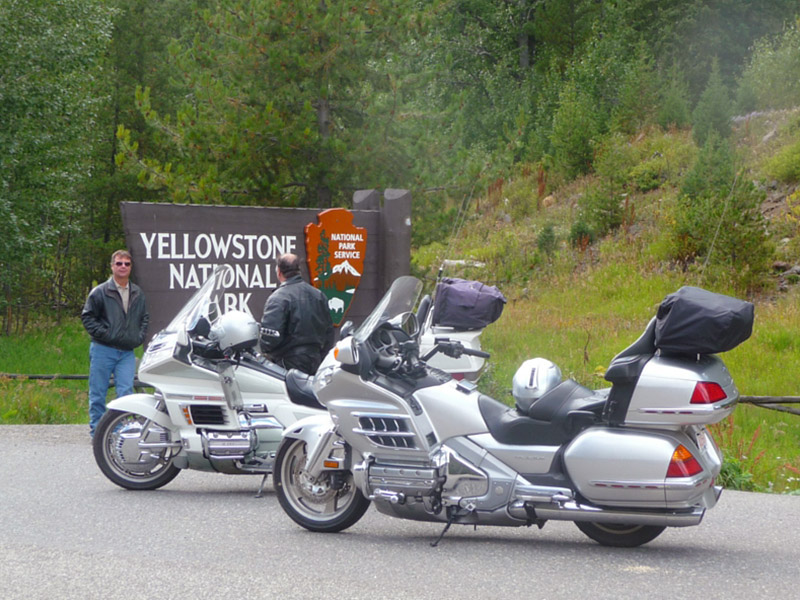 Mark Rovang next to the Yellowstone National Park sign in Wyoming with his motorcycle in the foreground.