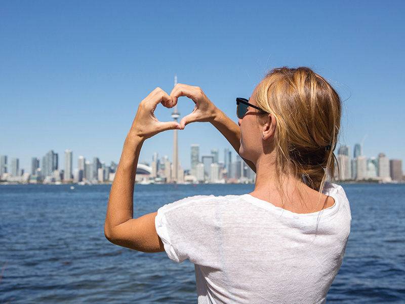 Woman looks at Toronto skyline and makes heart with her hands.
