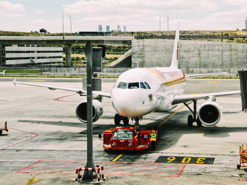 ): Airplane taxiing on an airport tarmac before departure for travellers' vacations