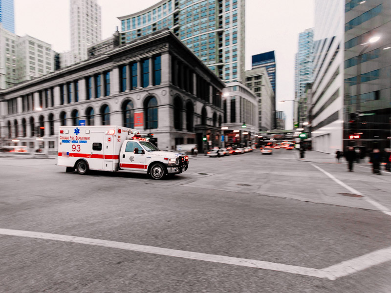 Ambulance parked in the center of a city street.