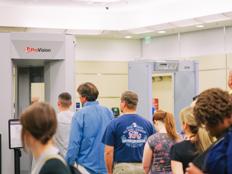 Travellers waiting in line to go through security screening at the airport.