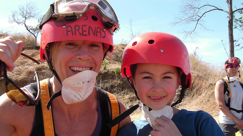 Mother and daughter wearing helmets smiling after completing an ATV ride in Costa Rica.