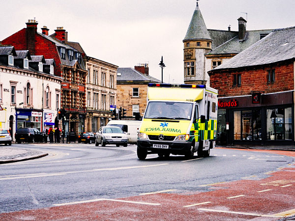 Yellow ambulance taking a traveller who had a medical emergency to hospital while travelling