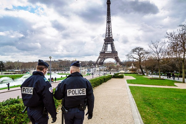 police walking together in front of Eiffel Tower