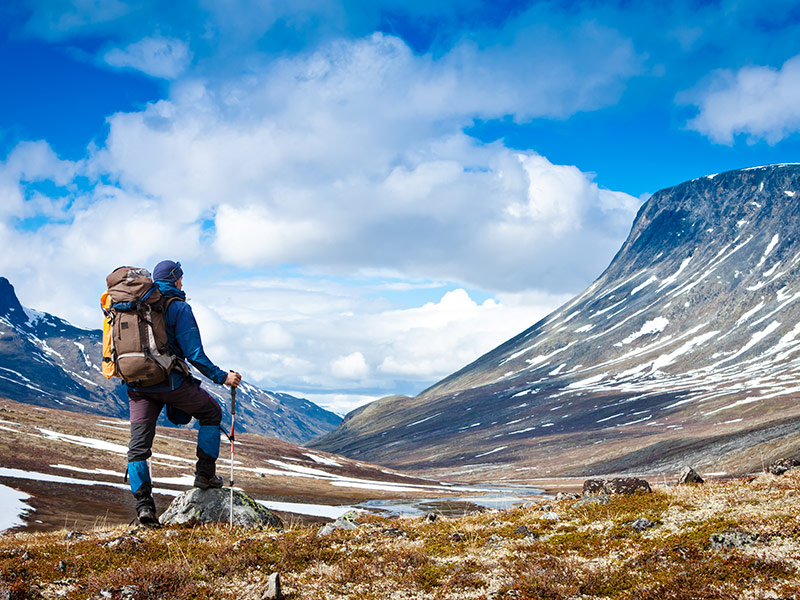 Hiker and mountain peak with snow
