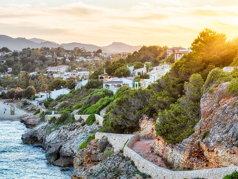 A path winds down to a beach in front homes in Mallorca, Spain, during sunset.