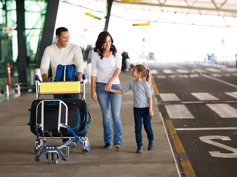 Young family at airport with a luggage trolley