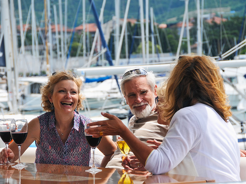 Two women and a man enjoy a glass of wine and laugh while on a boat