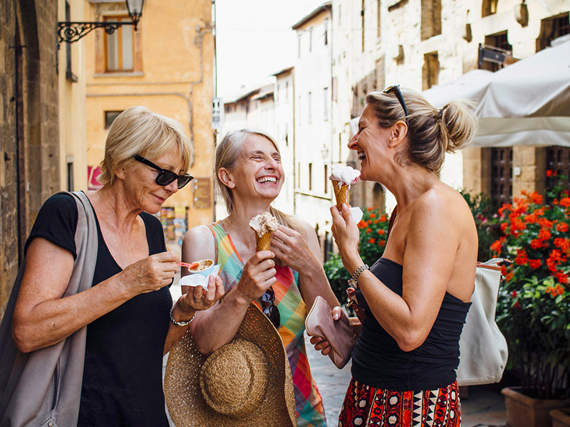three women laugh while eating ice cream in an Italian street