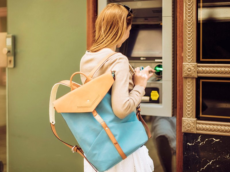 Woman using an ATM machine on vacation