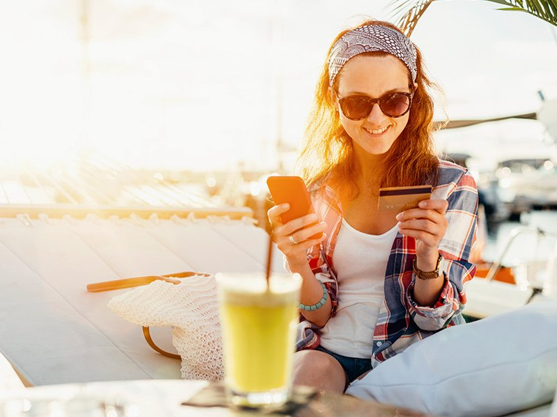 Woman using credit card on vacation
