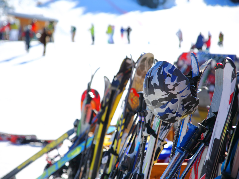 Skis and snowboards on ski rack with mountain in the background