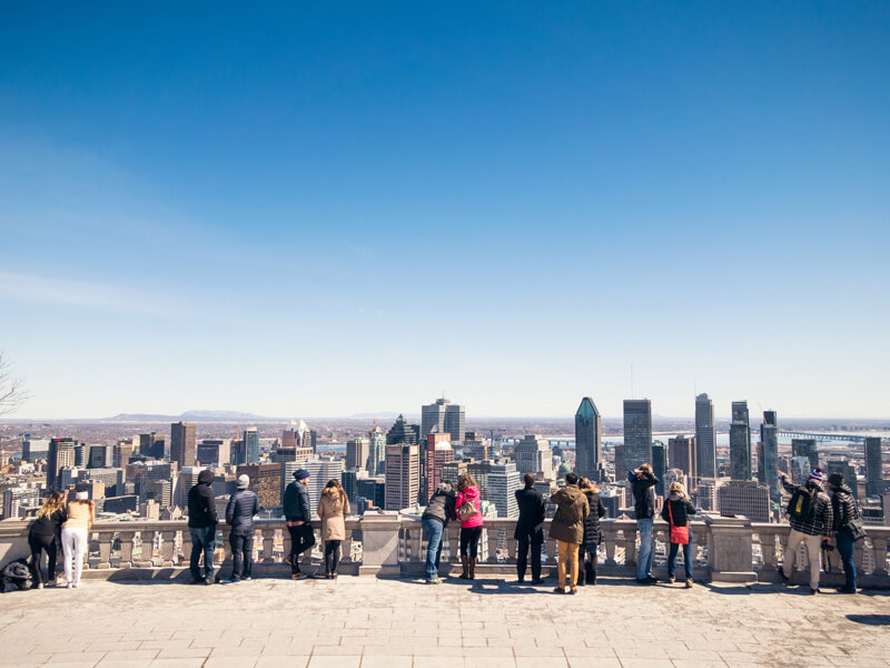 People overlooking the downtown area of Montreal in the Canadian province of Quebec, from a terrace on Mont Royal.