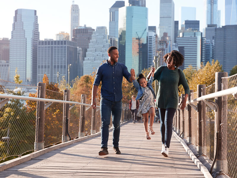 Family walks hand in hand on a footbridge in the city