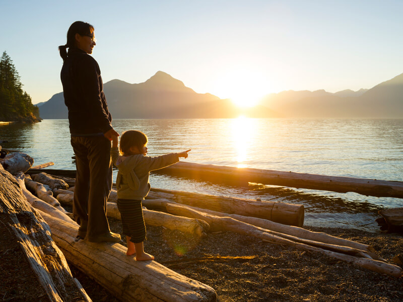 mother and daughter stand on log on beach at sunset