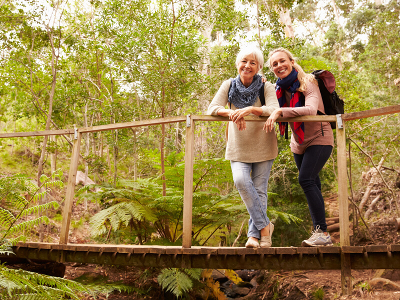 mother and daughter stand on wooden bridge in forest
