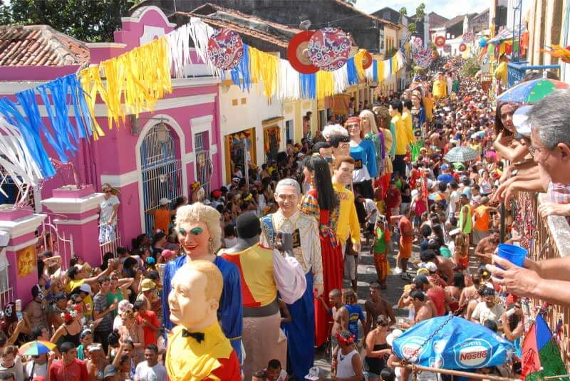 "Both Recife (above) and the neighbouring UNESCO World Heritage town of Olinda (below), in the northeastern state of Pernambuco, offer more traditional Carnival celebrations. Recife's famous symbol, the Galo da Madrugada (""Rooster of Dawn"") is considered the country's largest bloco, attracting millions of visitors, while Olinda, a much smaller colonial town, is famous for its giant papier-mache puppets."