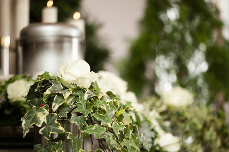 Urn with candles, ivy and white roses